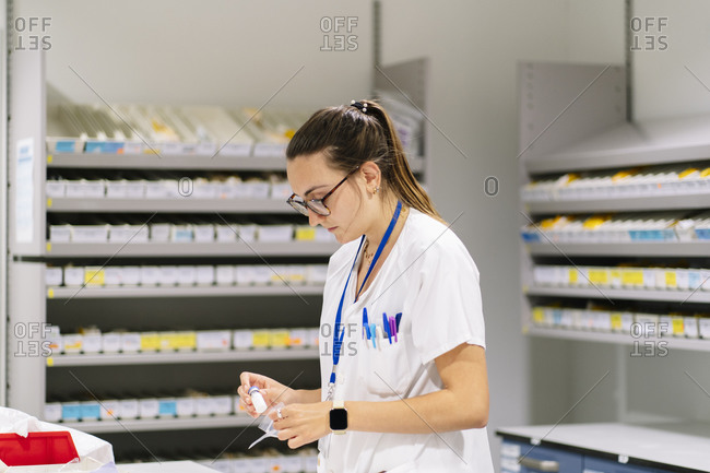 Female worker packing medicines while standing in pharmacy