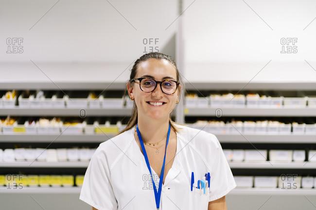 Smiling female pharmacist standing against medicine shelves in storage room