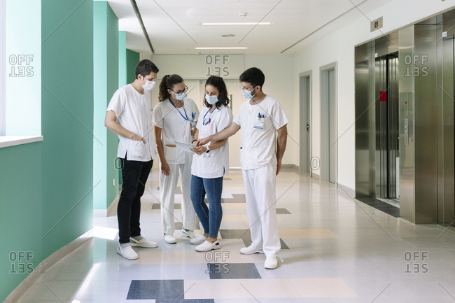 Doctors wearing surgical masks discussing over digital tablet while standing in corridor at hospital