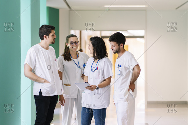 Doctors discussing over digital tablet while standing in corridor at hospital