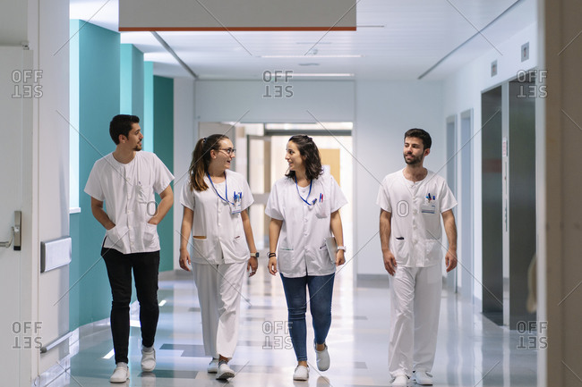 Doctors discussing while walking in corridor at hospital