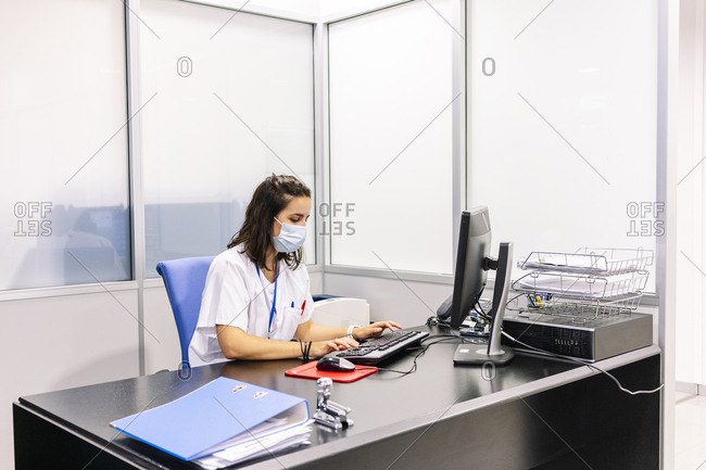 Female doctor wearing surgical mask using computer on desk in office at hospital