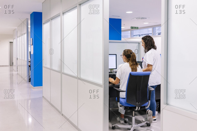 Female pharmacist discussing with coworker over computer in hospital seen through doorway
