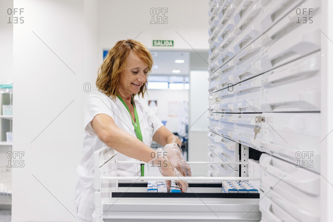 Smiling female pharmacist arranging medicines in drawers at laboratory