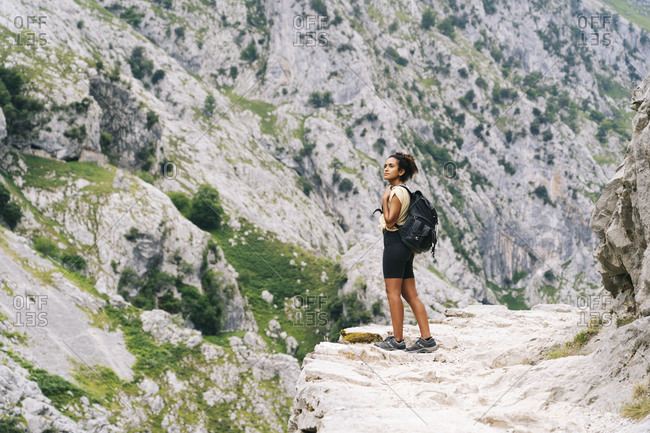 Woman with backpack admiring view while standing on mountain path at Ruta Del Cares- Asturias- Spain