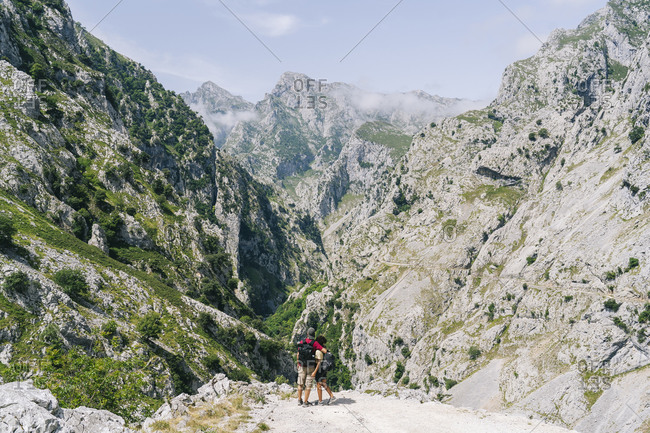 Couple looking at view while standing on mountain at Ruta Del Cares- Asturias- Spain
