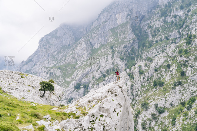 Young man admiring view while standing on mountain at Ruta Del Cares- Asturias- Spain