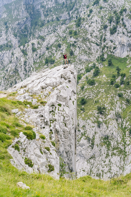 Man looking at view while standing on mountain peak at Ruta Del Cares- Asturias- Spain