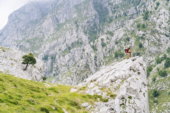 Man and woman standing on mountain peak at Ruta Del Cares- Asturias- Spain