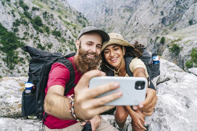 Couple smiling while taking selfie sitting on mountain peak at Ruta Del Cares- Asturias- Spain