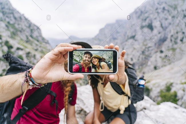 Couple taking selfie through phone while sitting on rock at Ruta Del Cares- Asturias- Spain