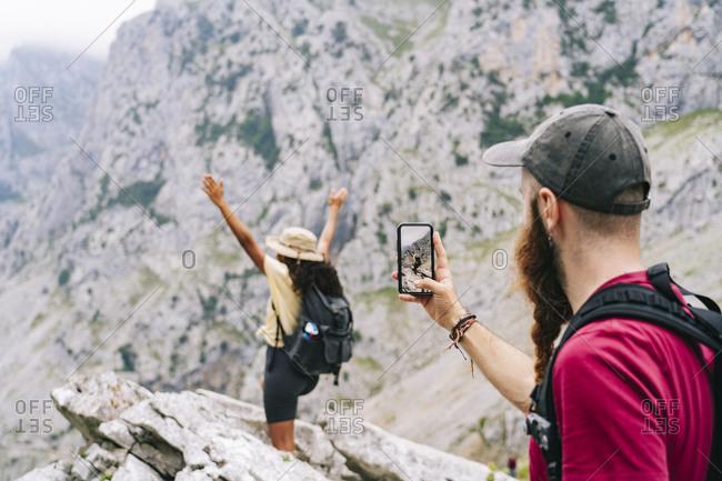 Man taking photo of woman standing on mountain peak at Ruta Del Cares- Asturias- Spain