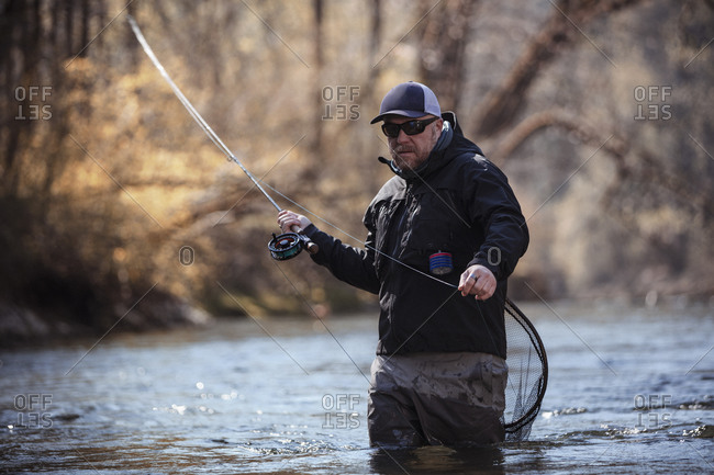 Fly fisherman holding fishing rod while standing in river at forest