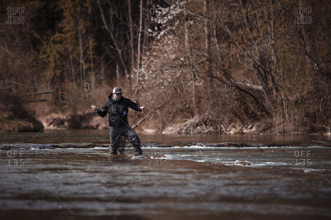 Fly fisherman holding fishing rod while casting in flowing river at forest