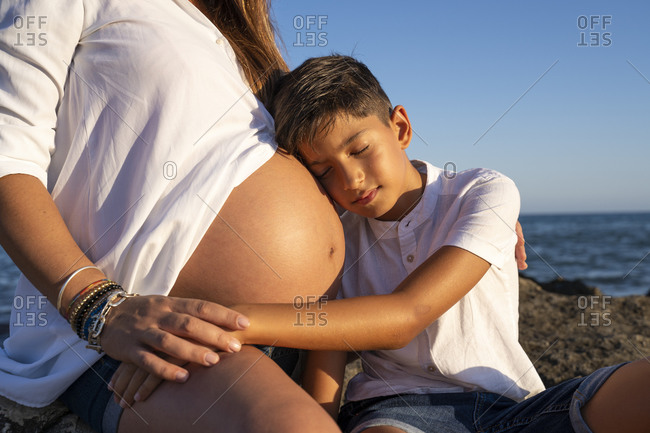Son keeping head on pregnant mother's stomach while sitting at beach