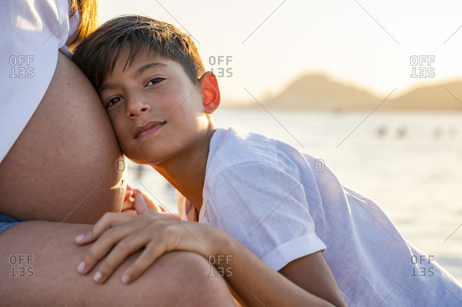 Son keeping head on pregnant mother's stomach while sitting at beach during sunset