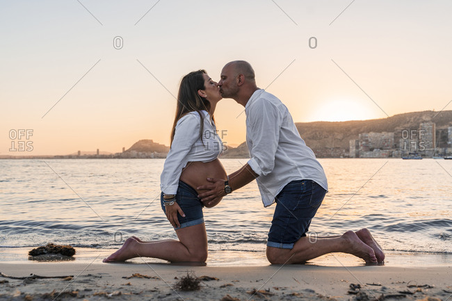 Mature man kissing pregnant woman while kneeling against beach during sunset