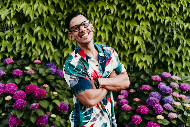 Smiling man with arms crossed standing against ivy hedge