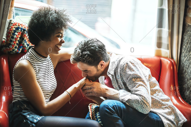 Romantic man kissing on girlfriend's hand while sitting in coffee shop