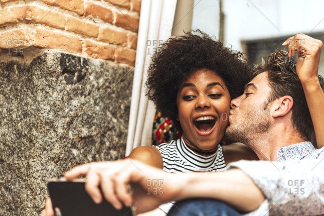 Close-up of man kissing cheerful girlfriend while taking selfie with her in coffee shop