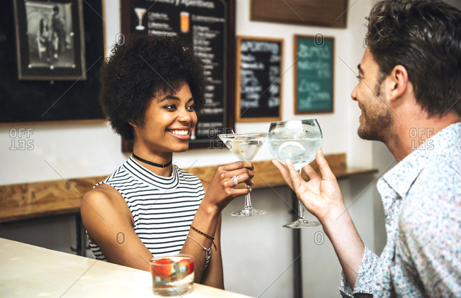 Happy couple toasting drinks while sitting at bar counter