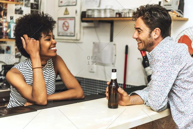 Man holding beer bottle flirting with smiling female bartender at bar counter