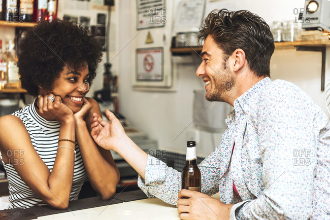 Man holding beer bottle touching female bartender while flirting with her at bar counter