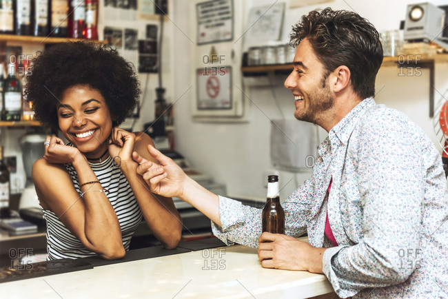 Man touching cheerful female bartender while flirting with her at bar counter
