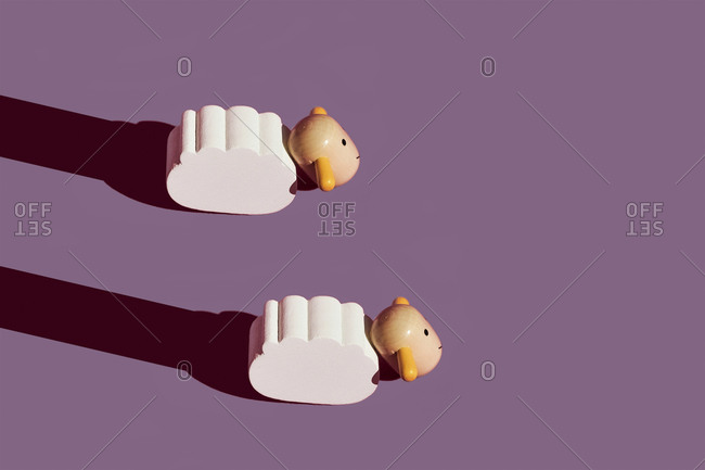 Studio shot of two small sheep figurines against purple background