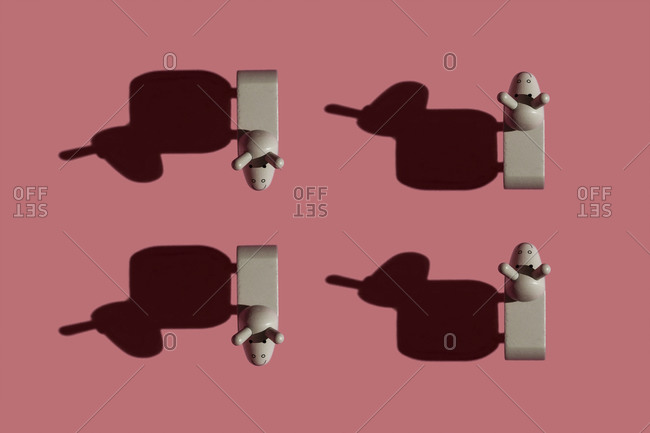 Studio shot of four small donkey figurines against pastel red background