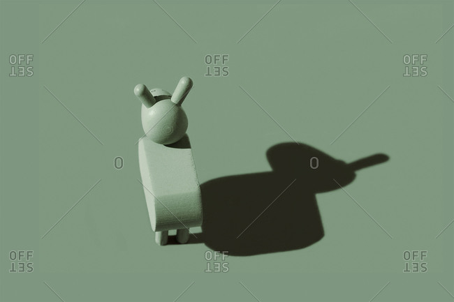 Studio shot of small donkey figurine against pastel green background