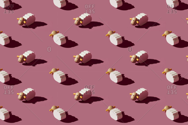 Pattern of small white sheep figurines against red background