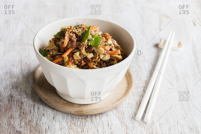Chopsticks and bowl of fried red rice with vegetables