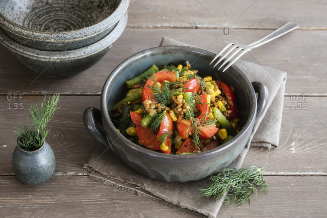 Bowl of ready-to-eat stir-fried vegetables with rye and dill