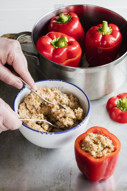 Hands of man preparing stuffed bell peppers with spelt