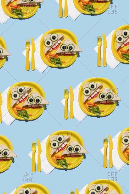 Pattern of plastic plates with funny looking sandwiches with anthropomorphic faces