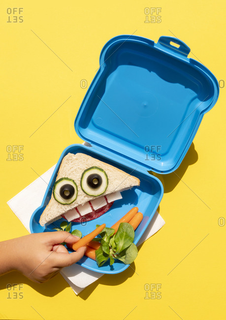 Hand of baby girl picking up baby carrot from lunch box with funny looking sandwich with anthropomorphic face