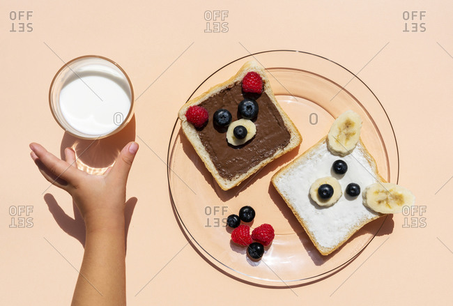 Studio shot of toasts with bear faces made of fruits and hand of baby girl reaching for glass of milk