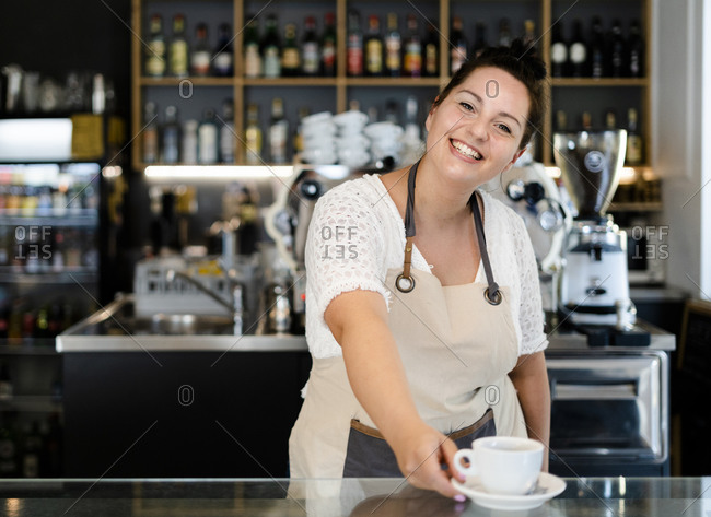 Smiling female owner serving coffee cup on bar counter while working in cafe