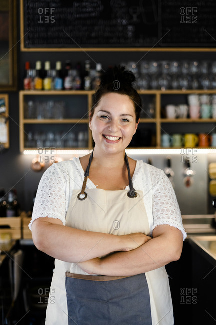 Smiling female owner with arms crossed standing in coffee shop