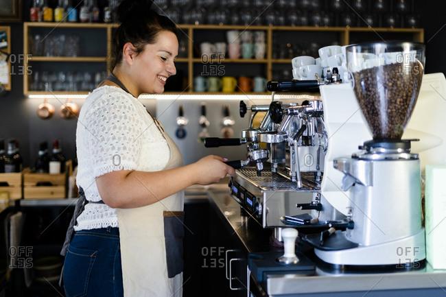 Smiling female barista making coffee through machine in cafe