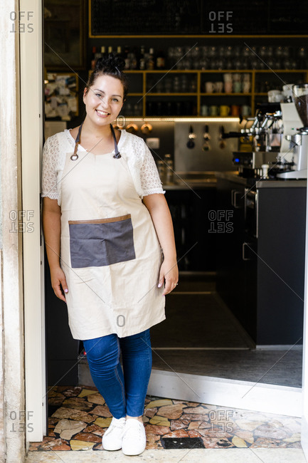 Smiling female owner standing by glass door at entrance of coffee shop