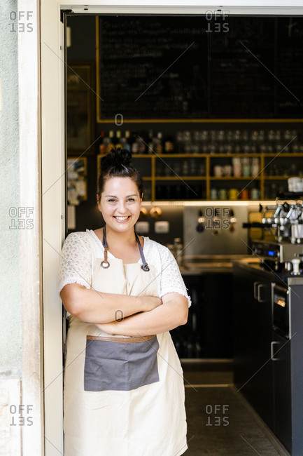 Smiling female owner with arms crossed standing at entrance of cafe