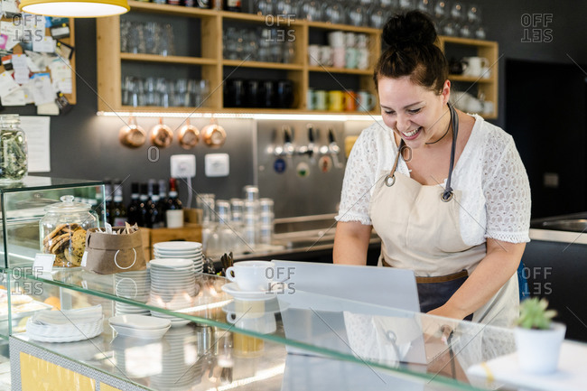 Cheerful female owner using laptop while standing in coffee shop