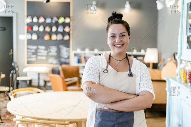 Smiling female owner with arms crossed standing against furniture in coffee shop