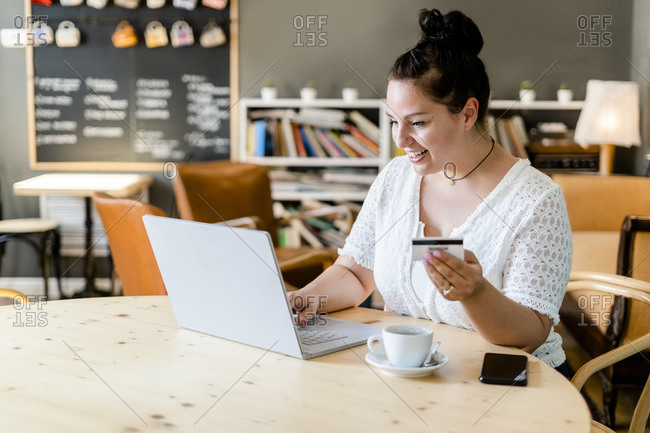 Happy young woman doing online shopping over laptop in coffee shop