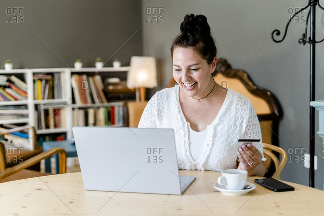 Happy voluptuous young woman doing online shopping over laptop in coffee shop
