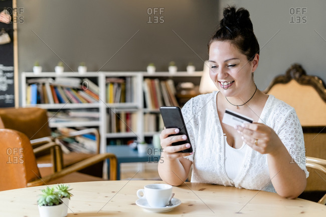 Smiling woman with coffee on table doing online shopping over mobile phone in cafe