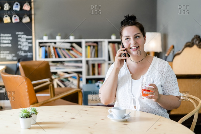Voluptuous woman holding drink talking over smart phone while sitting in coffee shop