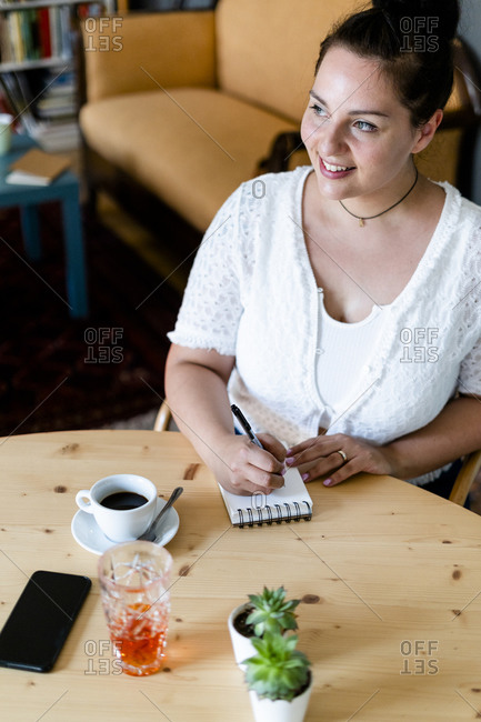 Young woman contemplating while writing in note pad on table at coffee shop